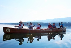 A group in a Voyageur canoe paddles across the glassy water of Yellowstone Lake.