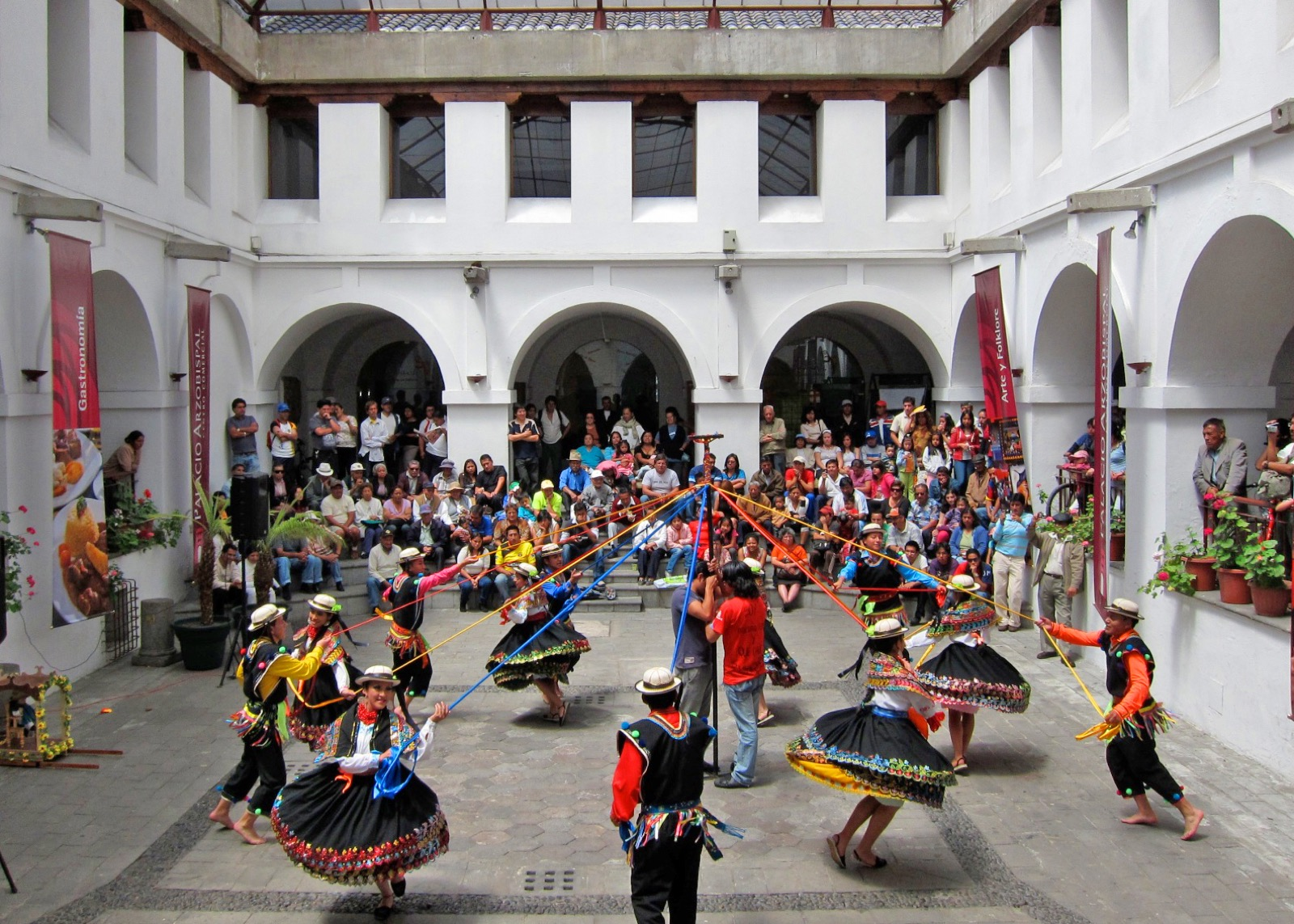 In a white-walled courtyard, visitors look on as Ecuadorian dancers in traditional outfits move around a pole, holding onto colorful ribbons.