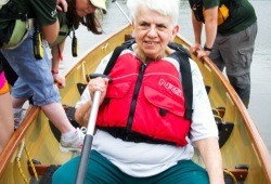 A woman sits in a canoe ready to paddle as the other participants enter