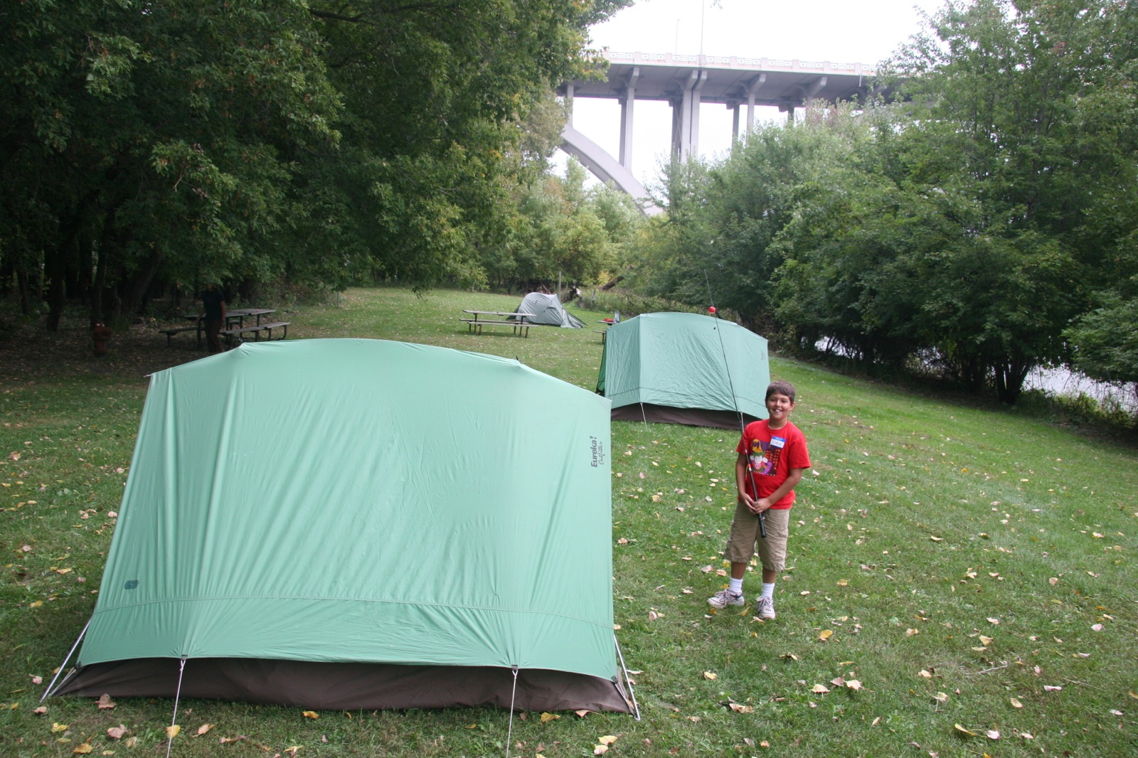A young boy stands next to his tent with a fishing pole at the campground near Fort Snelling.