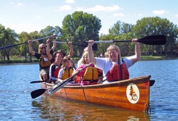 participants hold their paddles out of the water and smile for the camera while in a Voyageur canoe