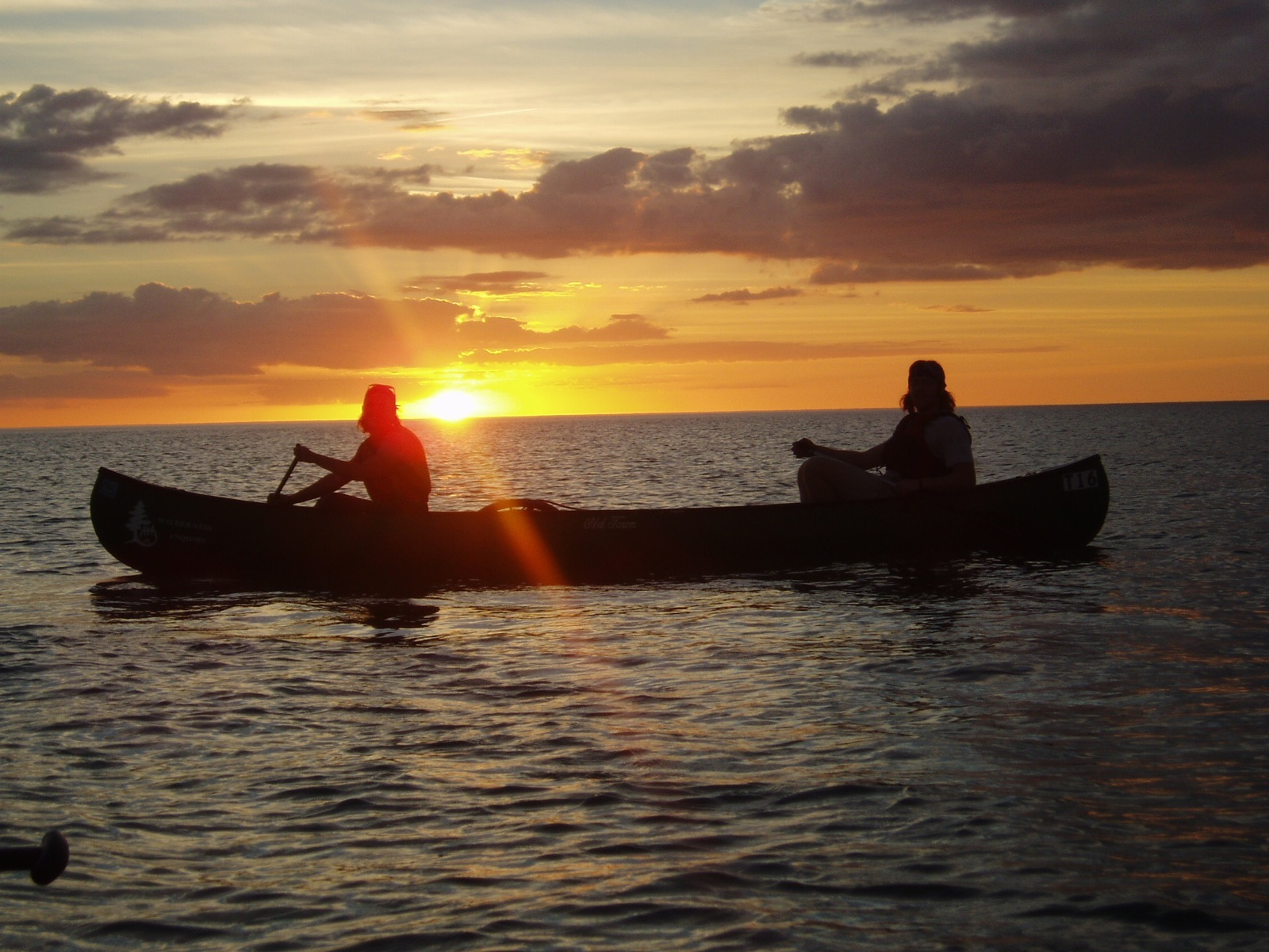 Two canoeists in a tandem canoe are silhouetted by the setting sun while paddling in the Gulf of Mexico.