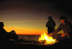The participants gather around a campfire on the beach at sunset.