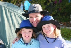A father and his two daughters smile in the sun at Wilderness Inquiry's campsite on Whitehorse Island.