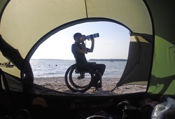 Photographer in a wheelchair takes a picture outside of a tent on the beach during Florida canoe trip.