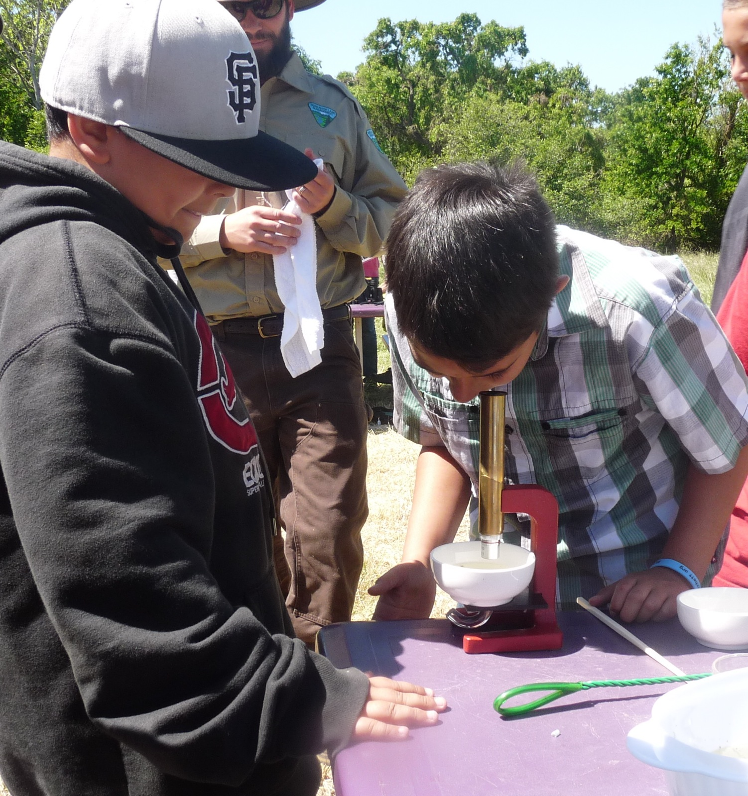 two boys use a microscope to identify macro invertebrates  in Galt