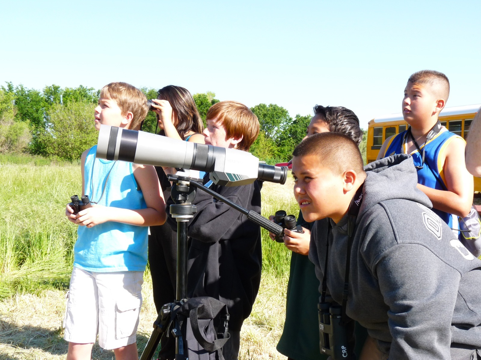 Students use binoculars to look for wildlife in a grassy area