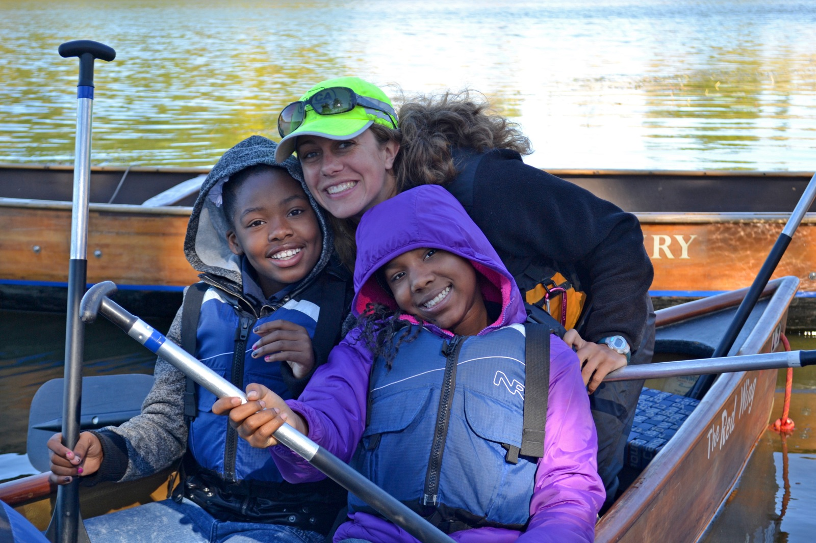 two participants smile in the stern of the canoe with a staff member near the shore