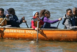 action shot of 6 participants paddling the canoe in Gary