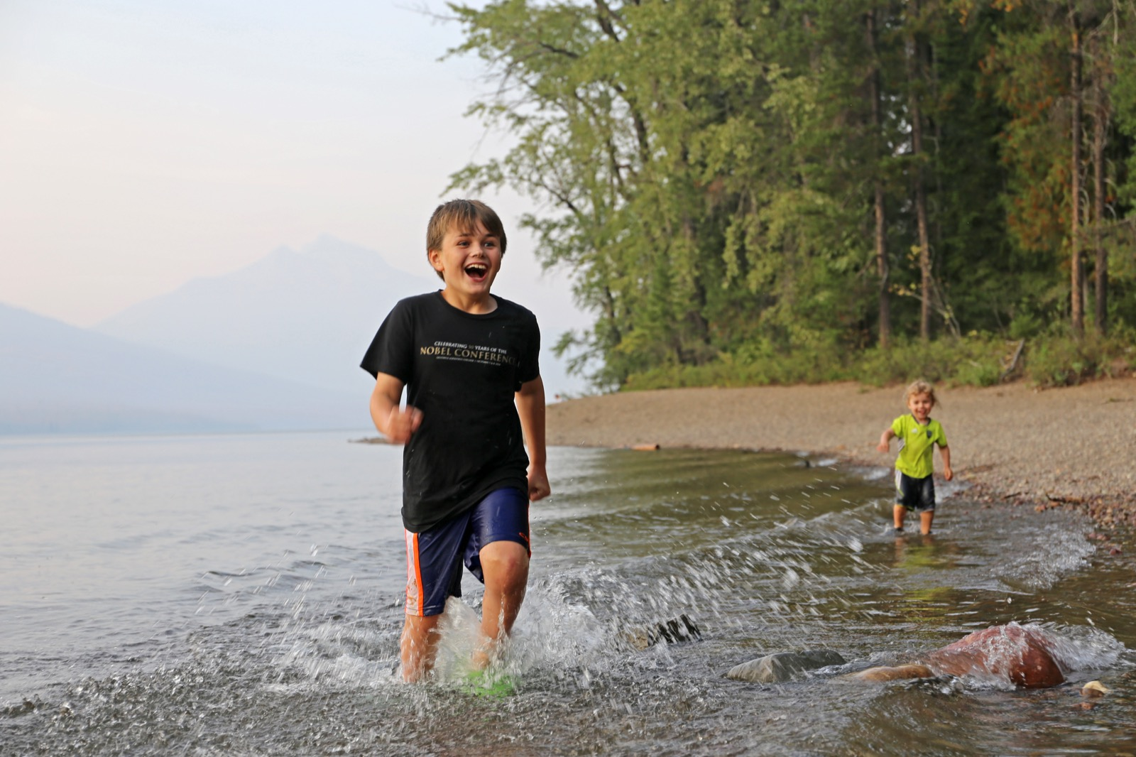 Two young kids splash in the shallow water along shores of St. Mary Lake in Glacier National Park.