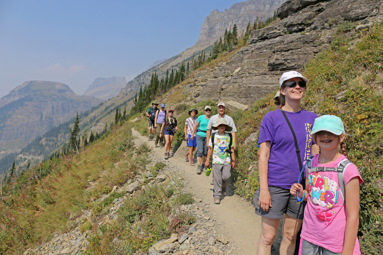 People of all ages hike up a mountain side in Glacier National Park.