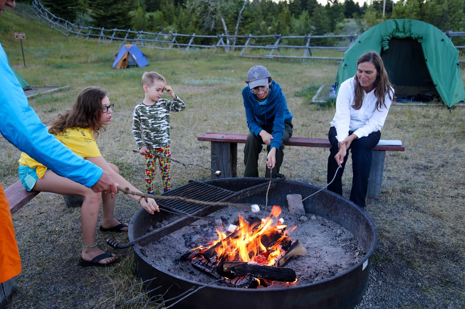 People of all ages roast s'mores over a fire ring in Glacier National Park.