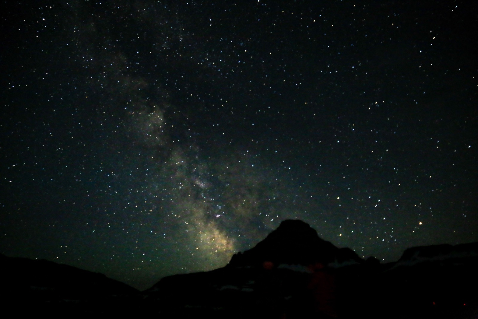 Stars and Milky Way in dark night sky over Glacier National Park.