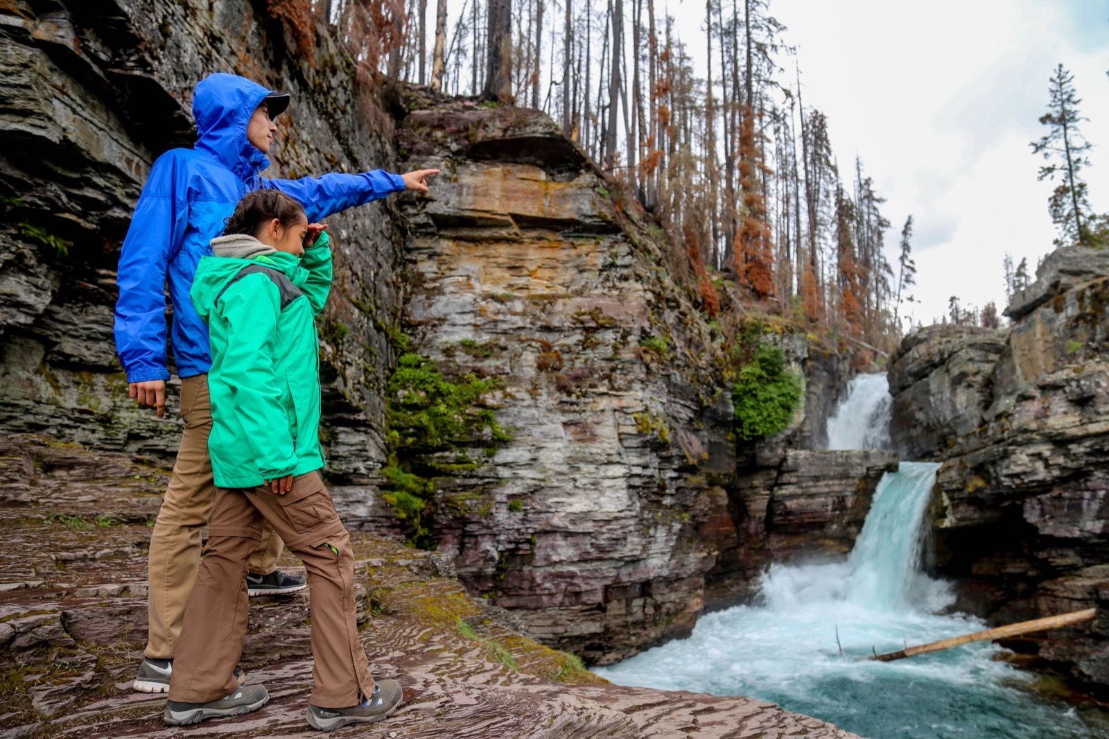 Father and daughter gaze out at St. Mary Falls in Glacier National Park.