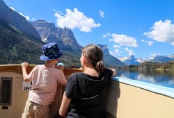Mother and young son pose at boat bow on tour of Lake McDonald in Glacier National Park.