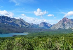 Beautiful gray mountains behind a lake in a grassy valley on a clear, sunny day in Glacier National Park.