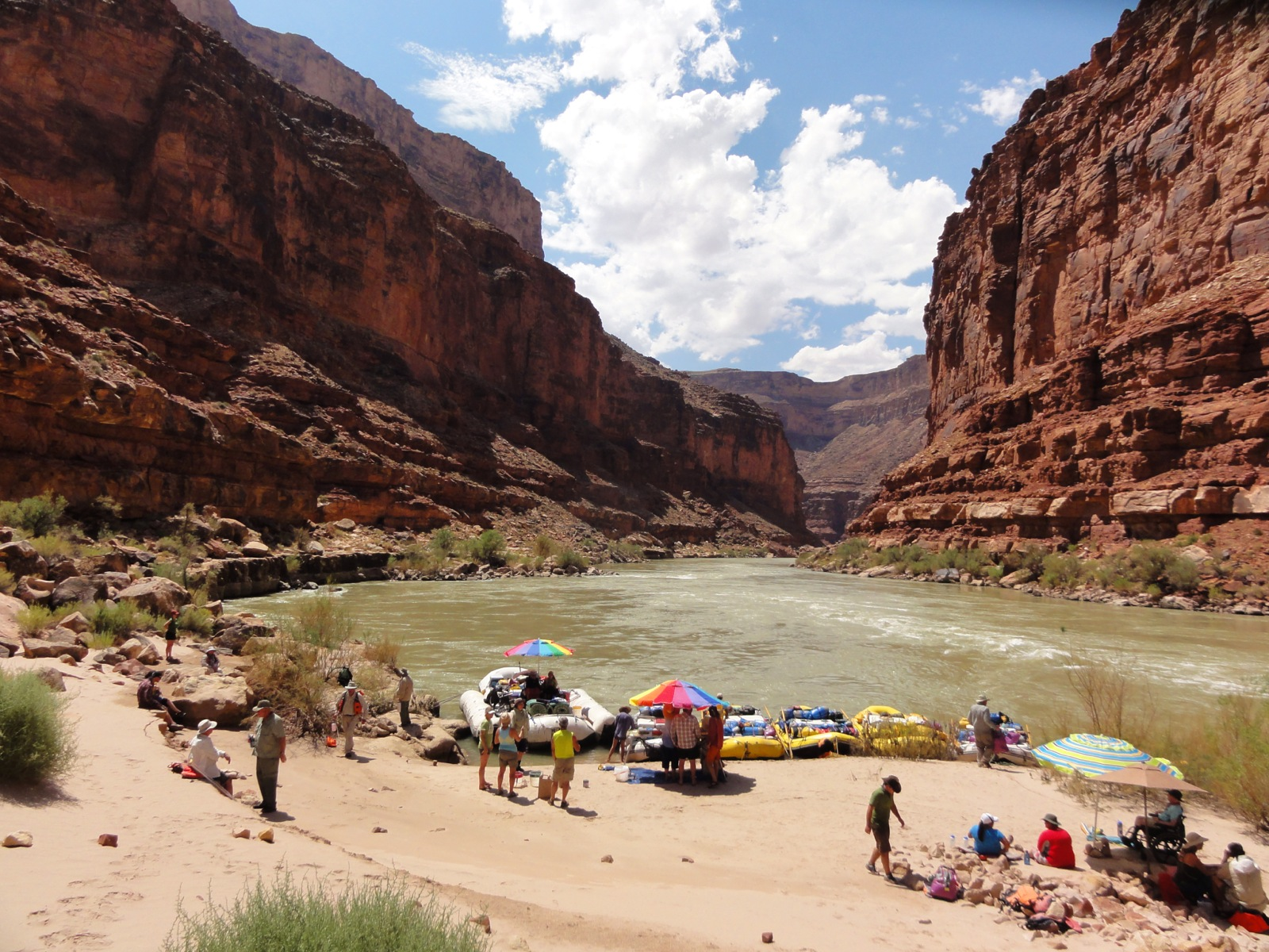 The group takes a lunch break on a sand beach with dramatic views of the canyon walls behind them.