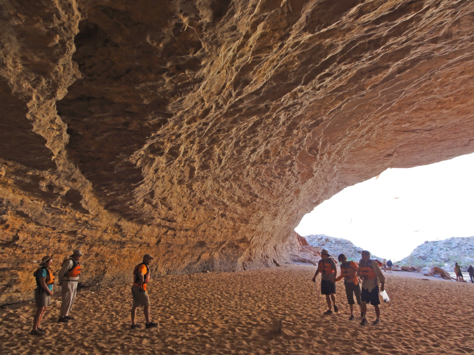 Several participants are dwarfed by the massive walls and ceiling of a cave on the edge of the Colorado River.