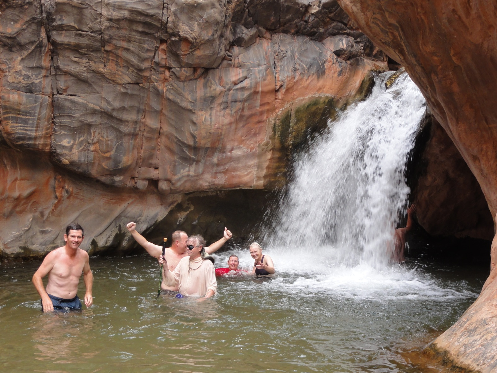 Five participants swim in the water below a small waterfall in a side canyon of the Grand Canyon.