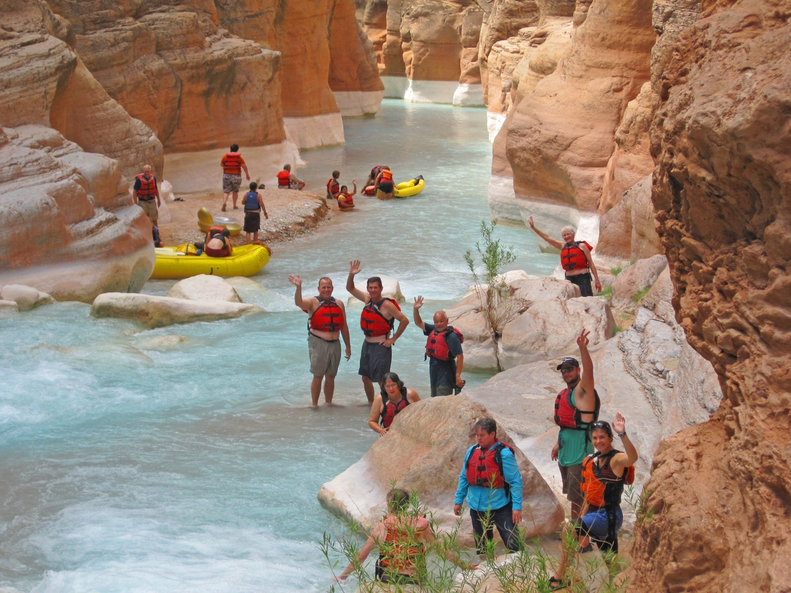 A large group of participants waves at the camera while wading in the calm, pale blue waters of Havasu Canyon, a welcome change from the rugged waters of the Colorado River.