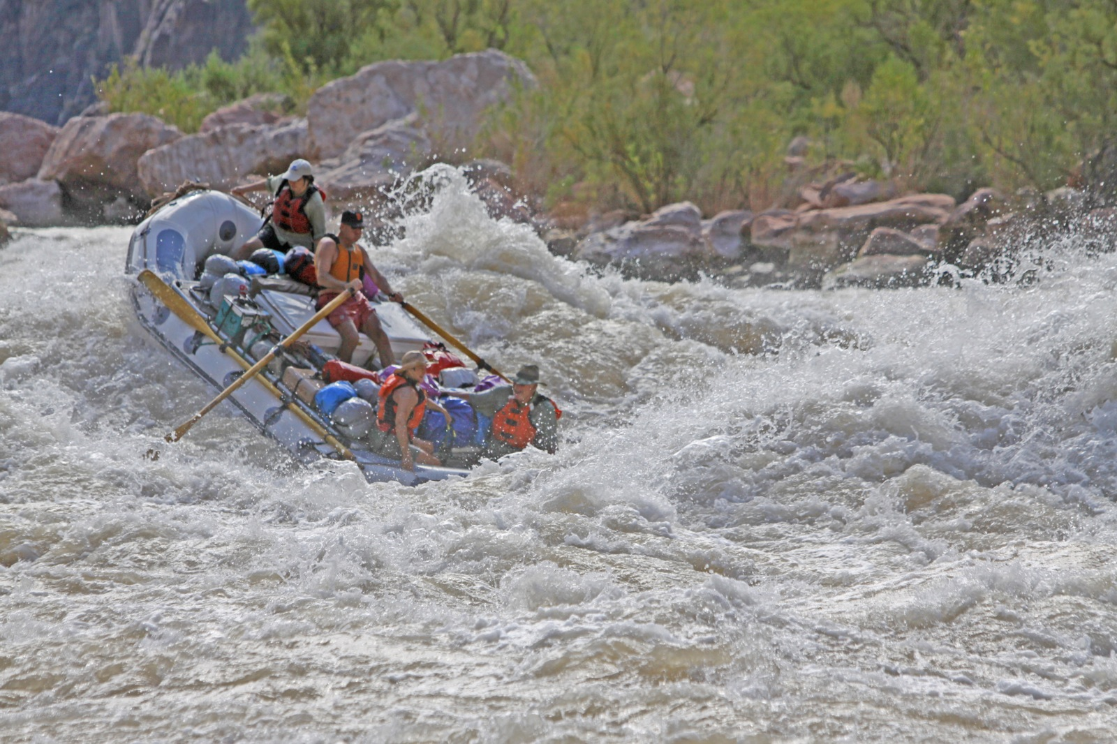 A guide on a gray raft oars through the raging water of Horn Creek rapids on the Colorado River as three participants hold on tight.