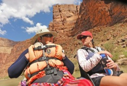 Two people with lifejackets, sunglasses, and hats, sit in a raft and talk with the steep walls of the Grand Canyon behind them.