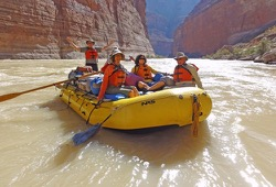 Five passengers in a yellow oar raft on the floating on the rushing river in the upper part of the Grand Canyon.