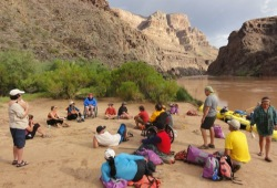 The group gathers on a sandy beach on the edge of the Colorado near Diamond Creek with rugge