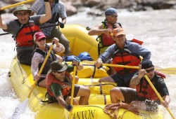 A yellow paddle raft with six participants and a guide excitedly paddle over the Lava Falls rapids.