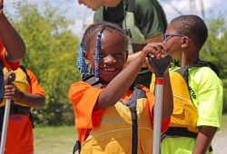 A young girl smiles as she gets ready for her first canoe ride.