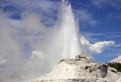 Castle Geyser exploding on a bright sunny day