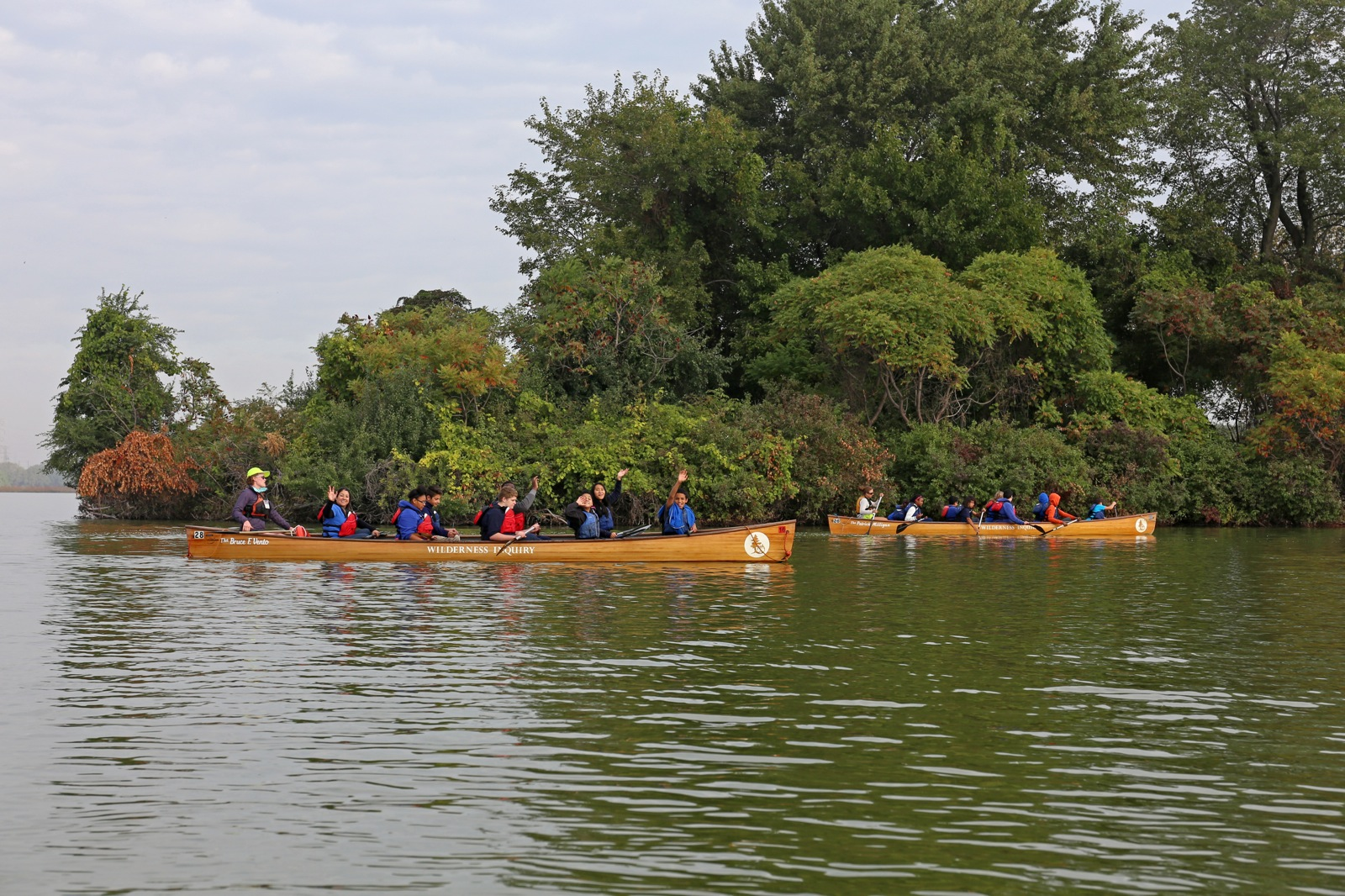 two voyageur canoes paddle near the vegetation on land in Wolf Lake Memorial Park