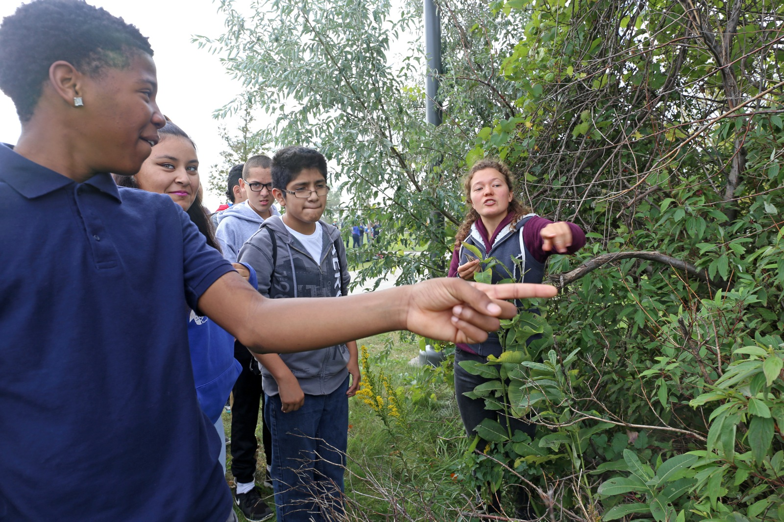 a boy points at a plant as the students learn about local wild plants