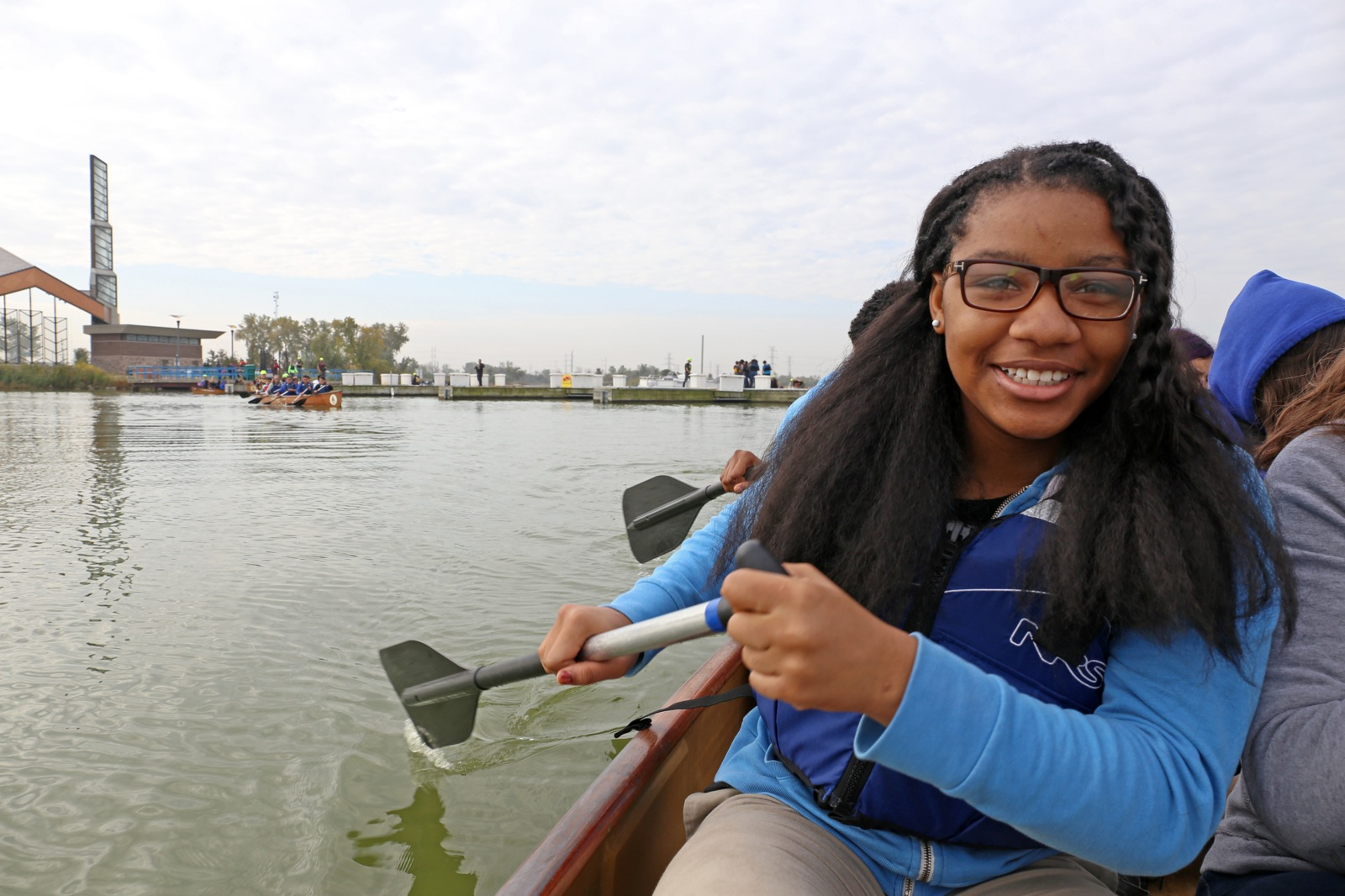 a girl smiles as she helps paddle the canoe