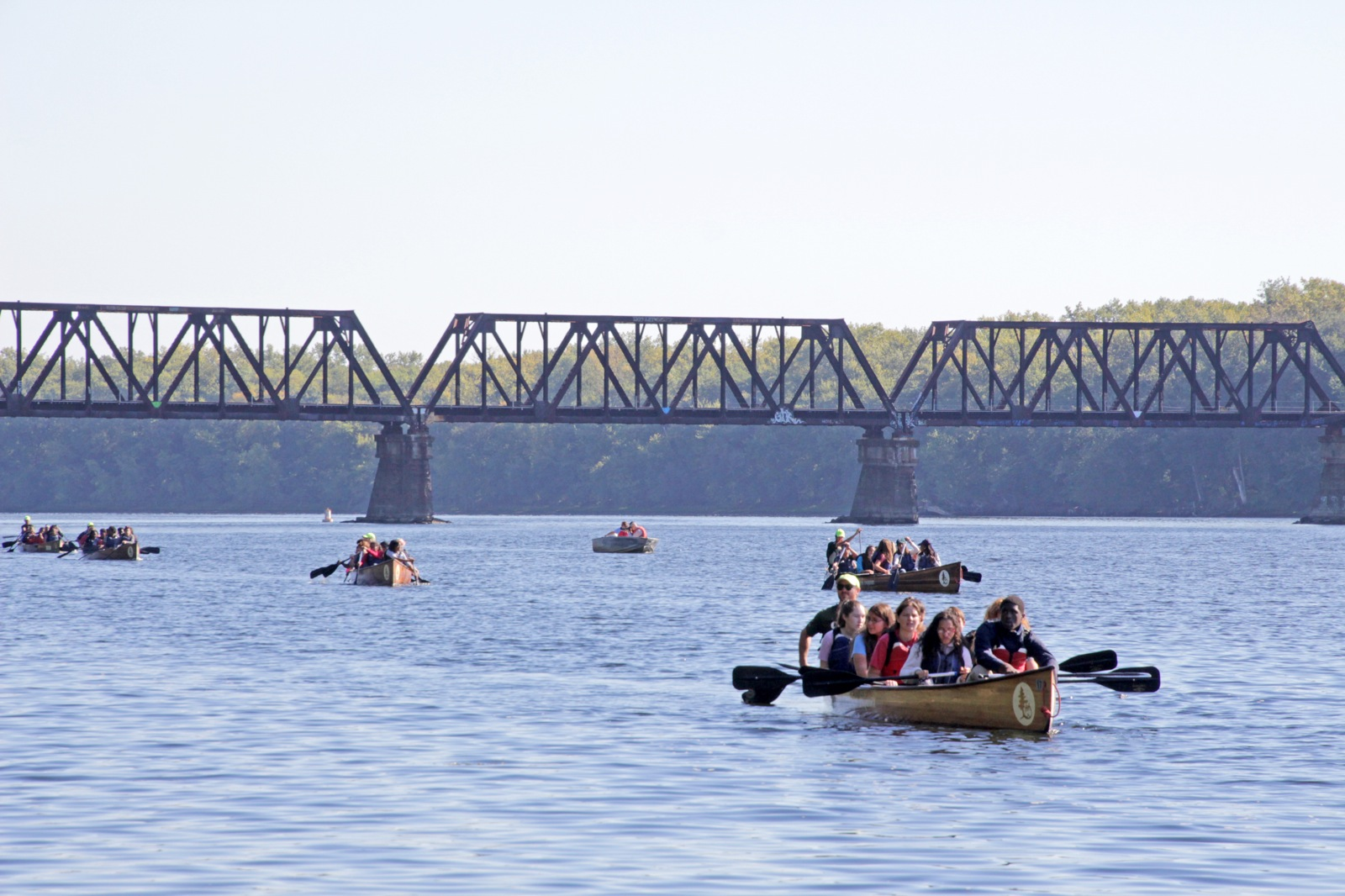 6 Voyageur canoes are spread along the river as they pass a bridge on a wide river