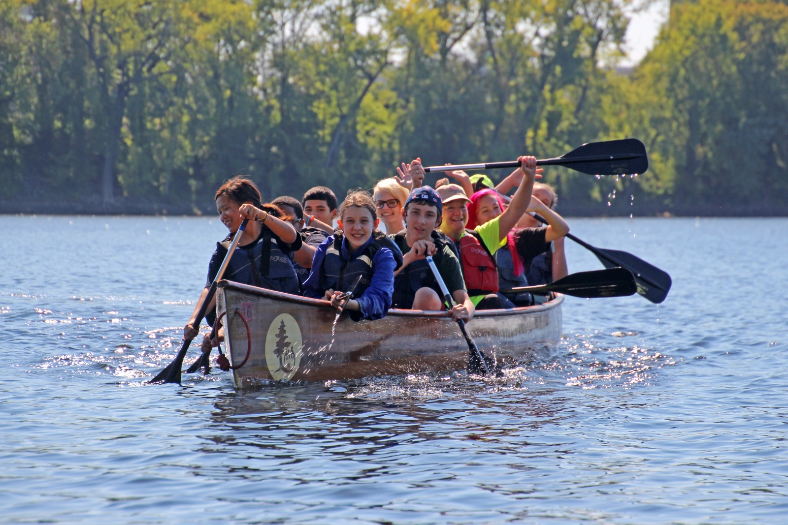 a group of students smile as they work together to paddle their canoe along a wide river