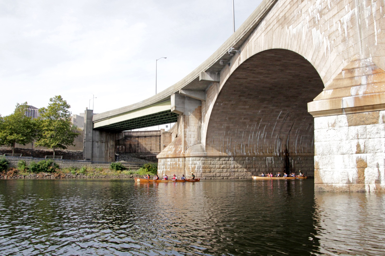 two voyageur canoes paddle underneath a large bridge in the distance
