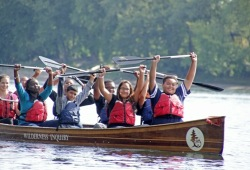 a group of students in a Voyageur canoe raise their paddles above their heads