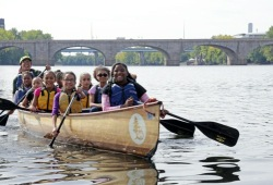 a group of youth smile as they paddle along the river near a bridge
