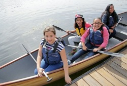 four girls smile as they sit in a canoe next to the dock waiting for others to get in the canoe