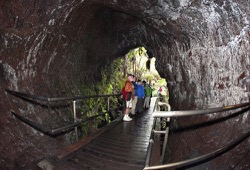 Hikers stand inside an old lava tube