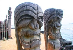 Two carved wooden idols sit on a beach at Pu'uhonua o Honaunau National Historical Park.