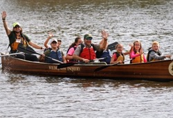 Youth and staff smile and wave at the camera as they paddle the voyageur canoe along the water