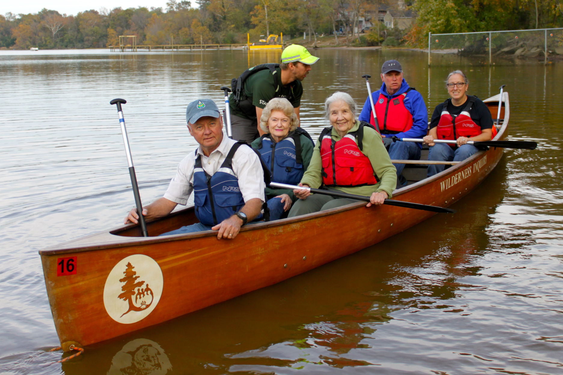a group of 5 adults sit in the canoe prepared to paddle