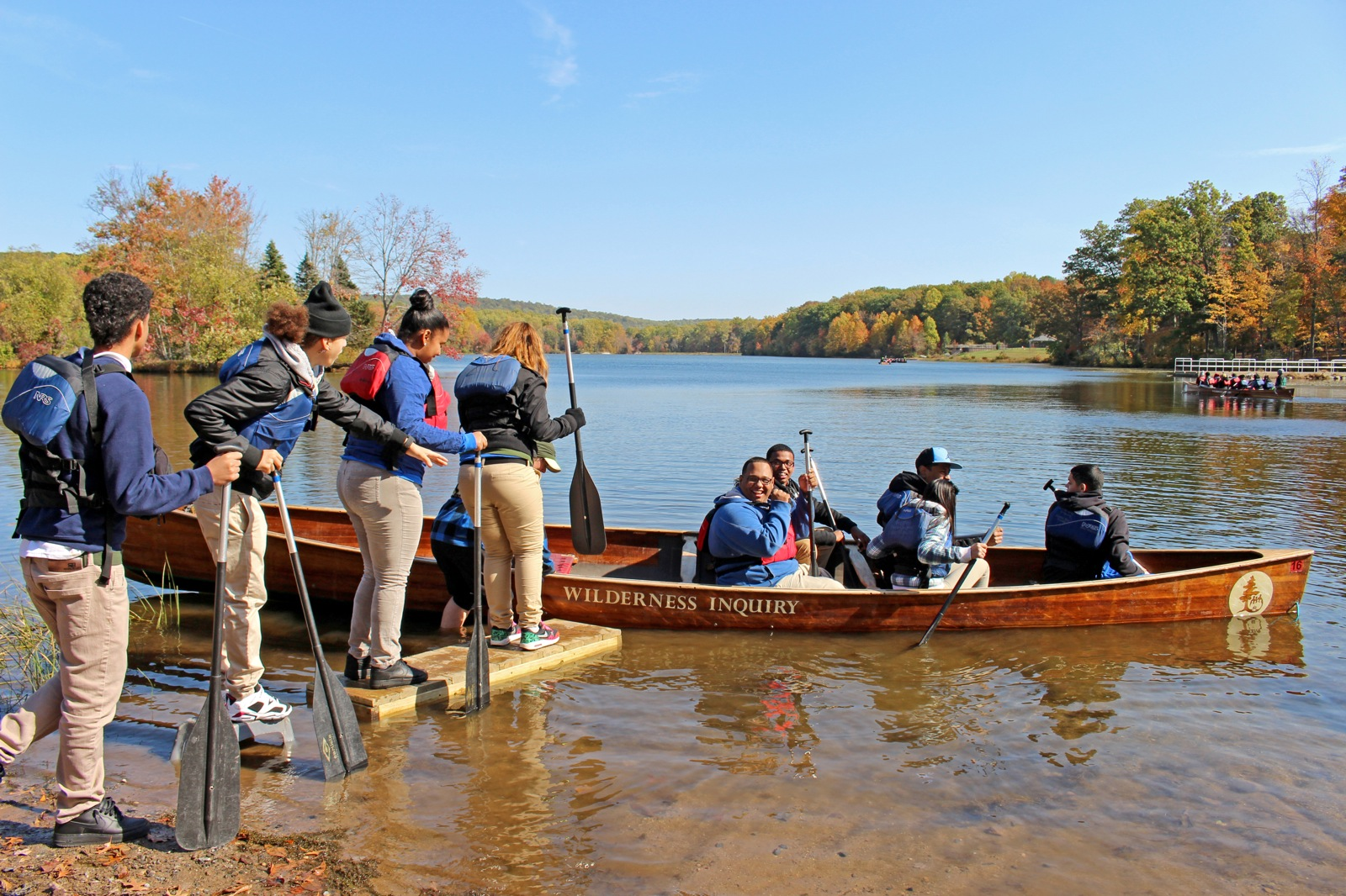 Participants load into the canoe on a sunny day