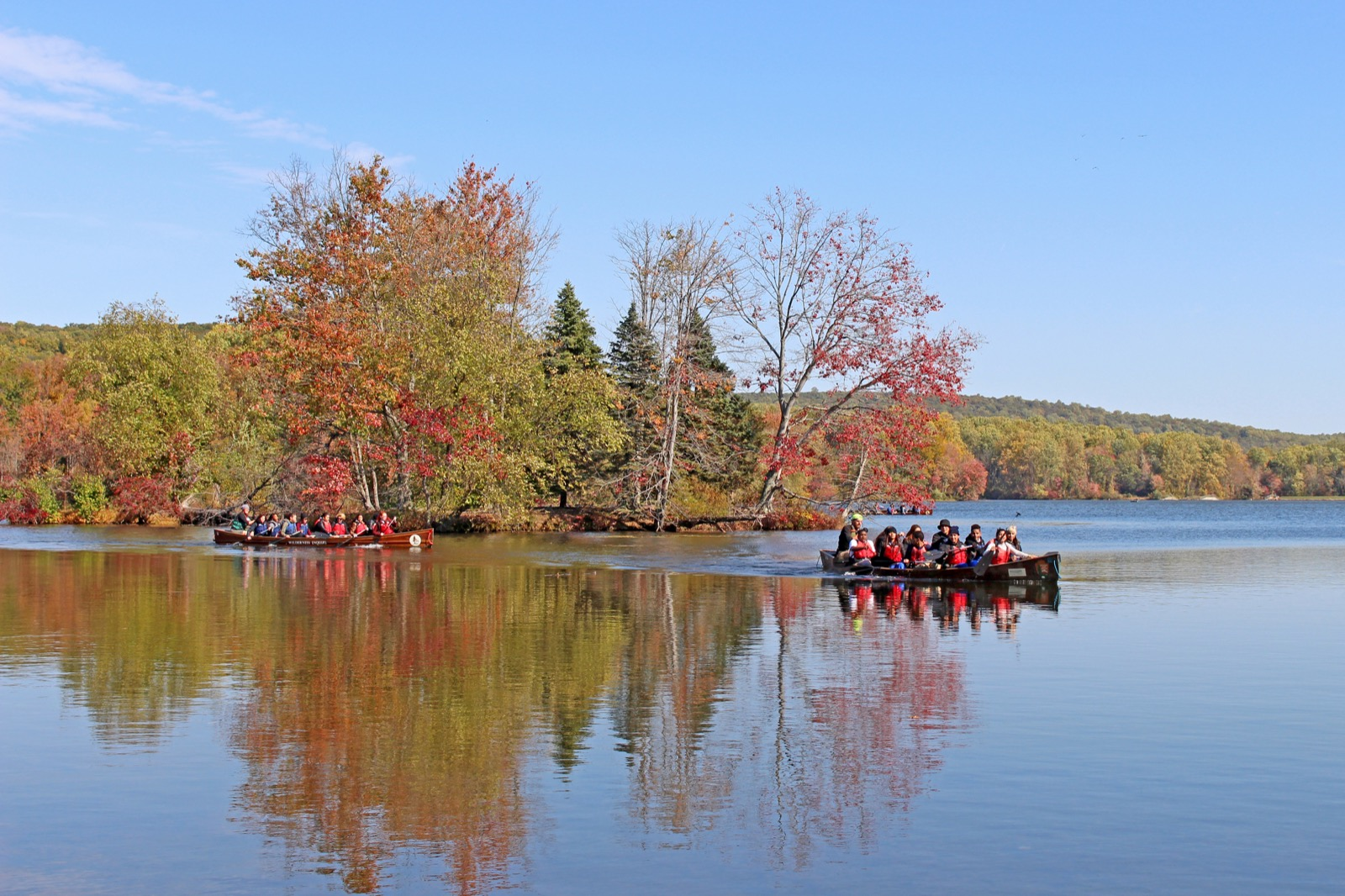 two Voyageur canoes paddle along a calm river in the fall