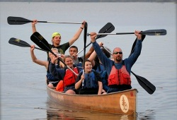 7 participants in a canoe hold their paddles up high while heading back to shore