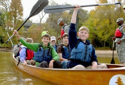 two boys in the bow of the canoe hold their paddles above their head