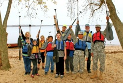 youth staff members and two U.S. Soldiers raise their paddles on the beach after a successful canoe
