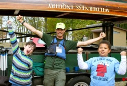 two boys show off their excitement for canoemobile with a staff member next to a  canoe